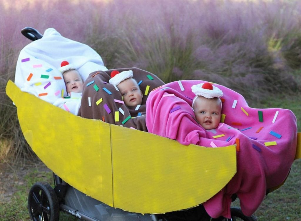 infant triplets dressed up as scoops of ice cream sitting in a triplet stroller that looks like a banana split