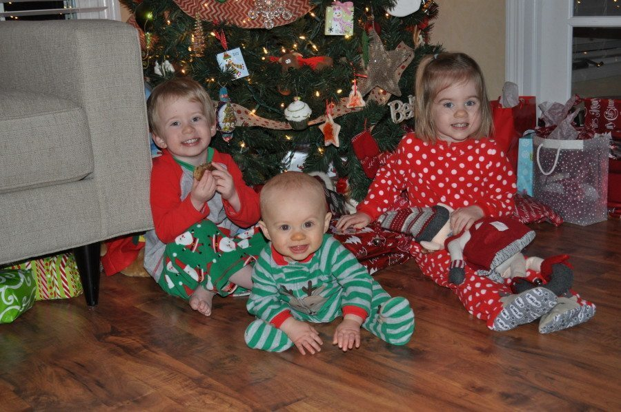 twin toddlers and a baby in pajamas under christmas tree third baby after twins