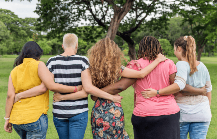 5 women facing away with arms around each other friends