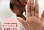 woman vomiting in a toilet and hold her hand up hyperemesis