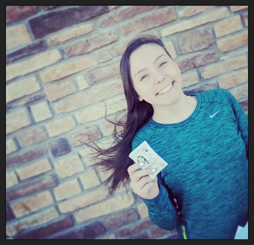 teen driver smiling and holding new drivers license