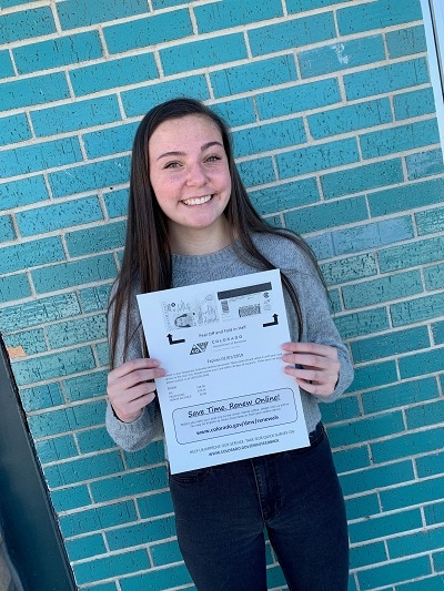 teen driver smiling while holding her new drivers license