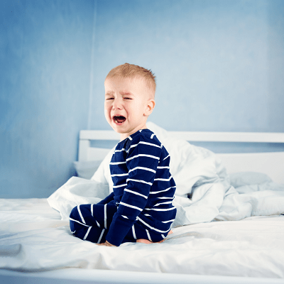 toddler bed for twins boy kneeling on bed crying