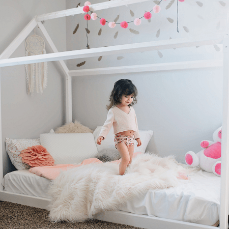 toddler bed for twins girl standing on white toddler bed smiling