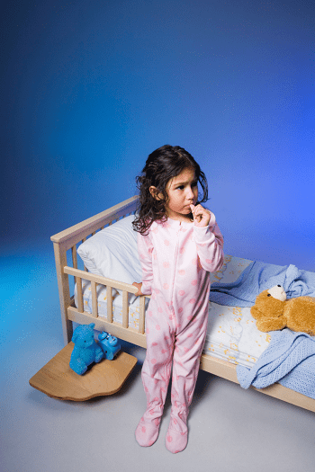 toddler bed for twins girl standing next to toddler bed with pink pajamas on