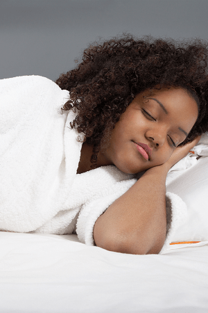 twin pregnancy symptoms woman sleeping on her side with a hand under her cheek