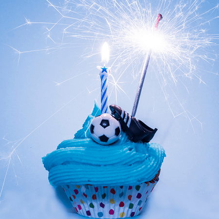 twins' birthday soccer themed cupcake with candles, soccer ball, and cleats.
