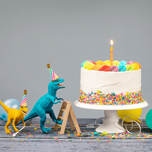twins' birthday dinosaur figures wearing birthday hats, balloons, a white birthday cake with a candle and confetti on a table