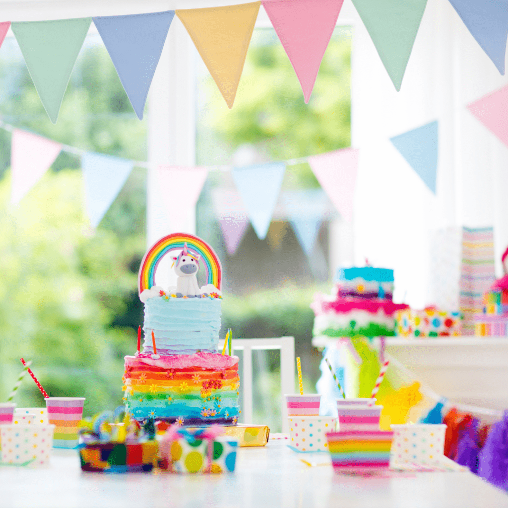 twins' birthday cake with a rainbow and unicorn on top, and cups with colored straws on a table