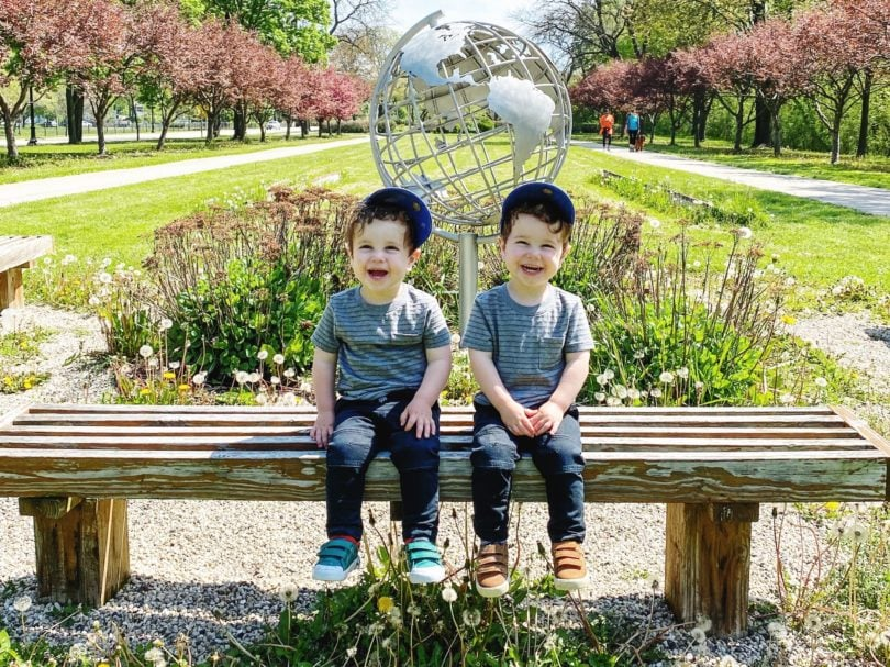 twin toddler boys sitting on a bench dressing twins alike