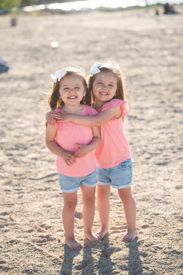 twin toddler girls hugging on the beach dressing twins alike