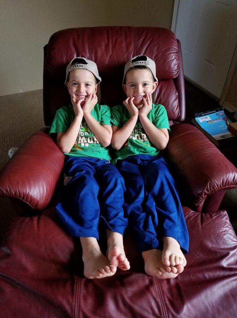 twin boys sitting in a recliner dressing twins alike