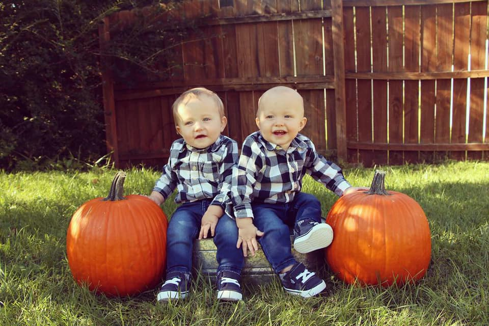 twin toddlers sitting by pumpkins dressing twins alike