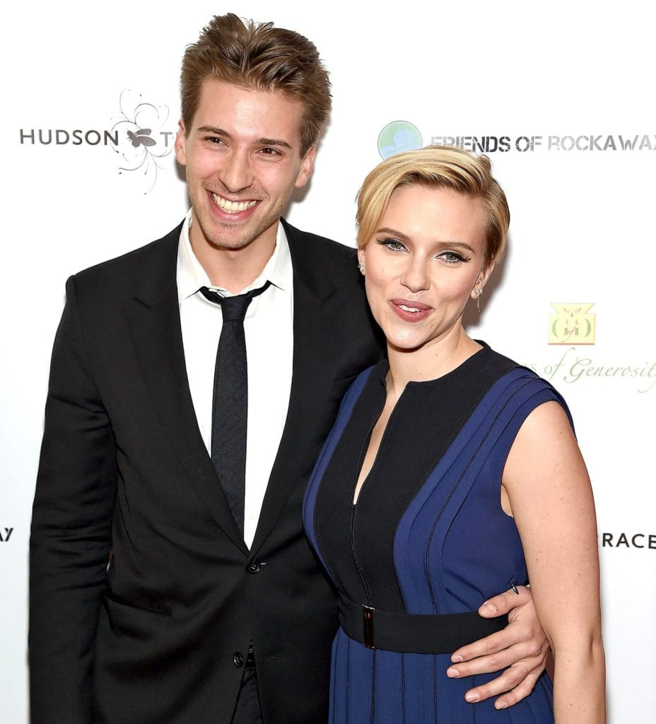 celebrity twins Scarlett Johansson and Hunter Johansson smiling arm in arm on a red carpet.