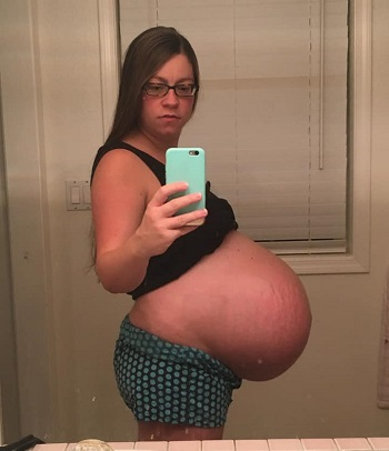 pregnant with twins belly. A pregnant woman holding her phone for a picture showing off very pregnant belly