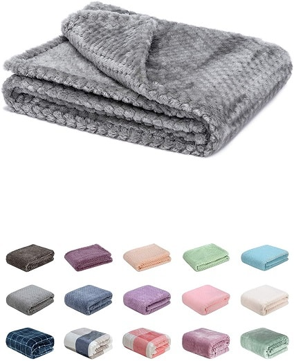 stroller blanket a grey folded baby blanket with 15 different smaller blanket underneath showing different color choices.