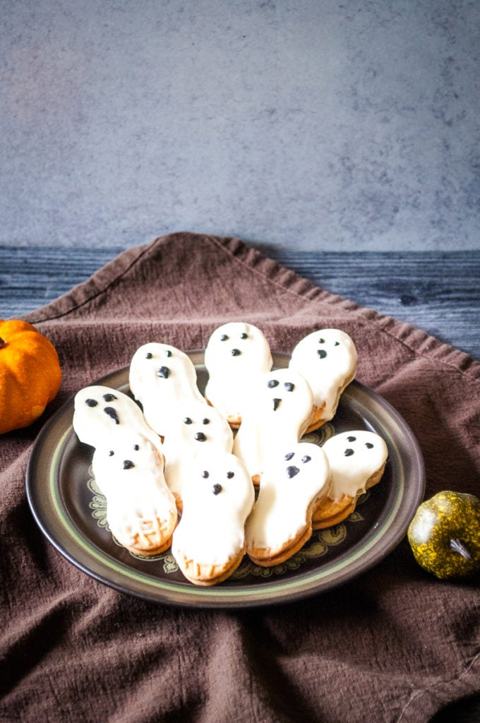 ghost cookies nutter butters on a plate dripping with white chocolate and eyes and a nose drawn on