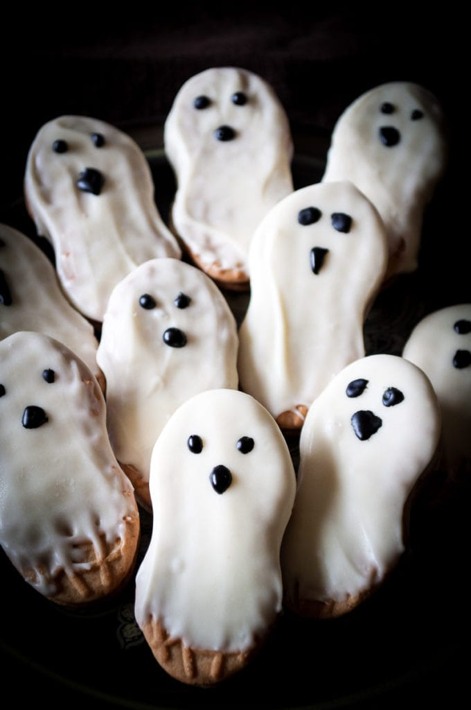 ghost cookies nutter butters dripping with white chocolate and eyes and a nose drawn on