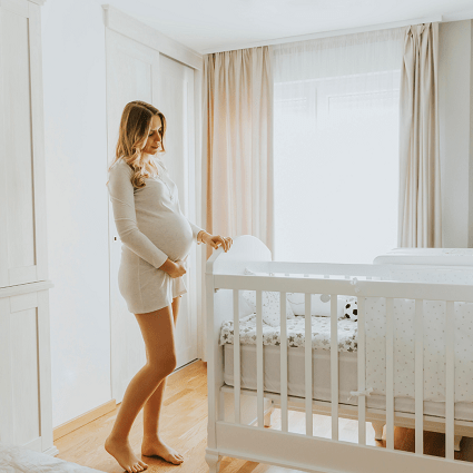 crib mattress dimensions. pregnant woman looking at put together crib while holding belly