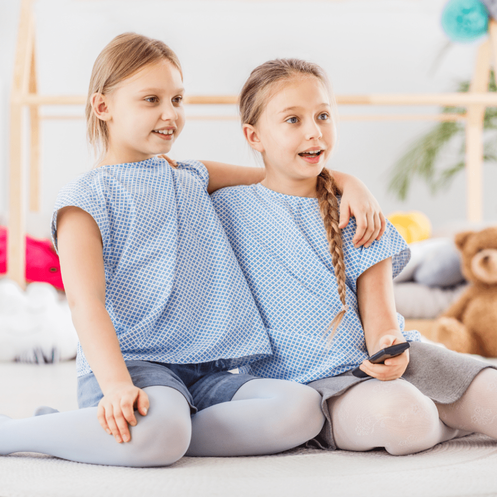 twins tv show twin girls smiling and holding tv remote