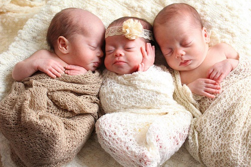 having triplets 3 infants, 2 boys and 1 girl, wrapped in blankets and laying on a large blanket together