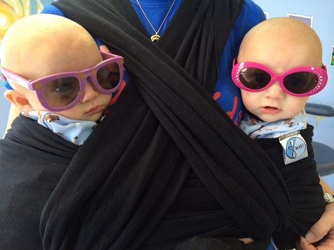 babywearing benefits twin infants in a babywearing wrap with sunglasses one