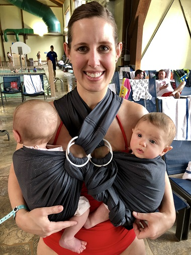 babywearing benefits woman wearing infant twins smiling at the camera