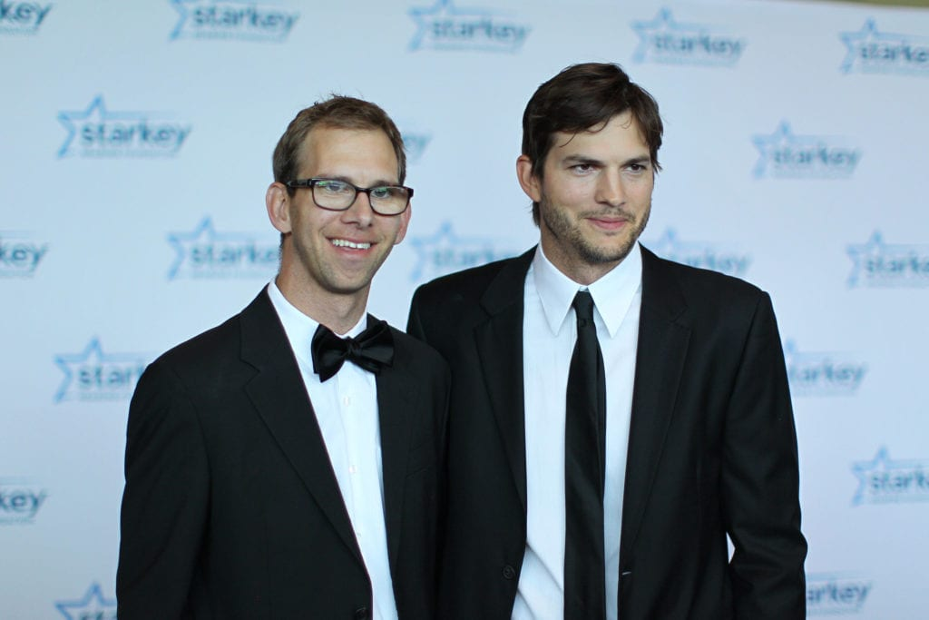 Celebrity twins two men in tuxedos on a red carpet posing for a picture while smiling.