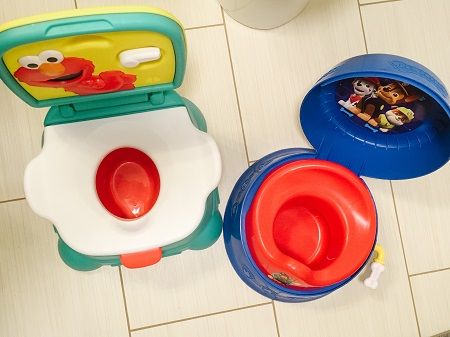 potty training regression two colorful potty seats on a floor, next to one another