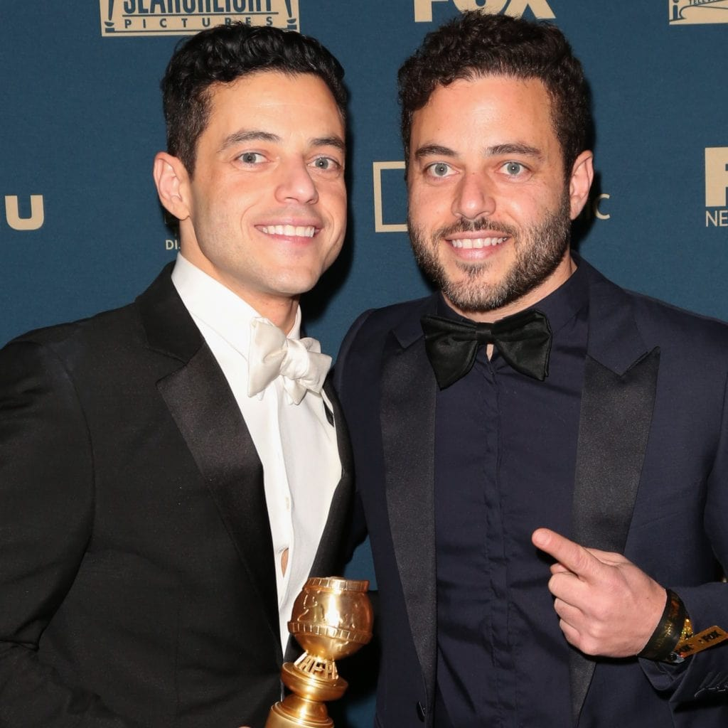 Celebrity twins identical twins in tuxedos smiling, 1 holding an award.