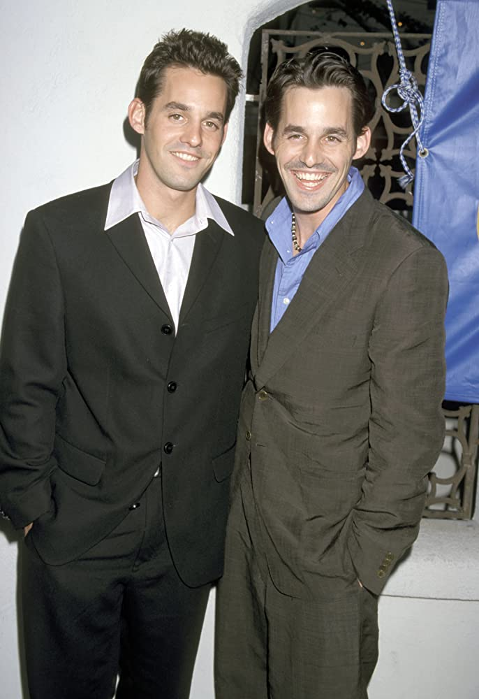 celebrity twin 2 men smiling at a camera in dark suits, 1 wearing a blue shirt, the other a white shirt.