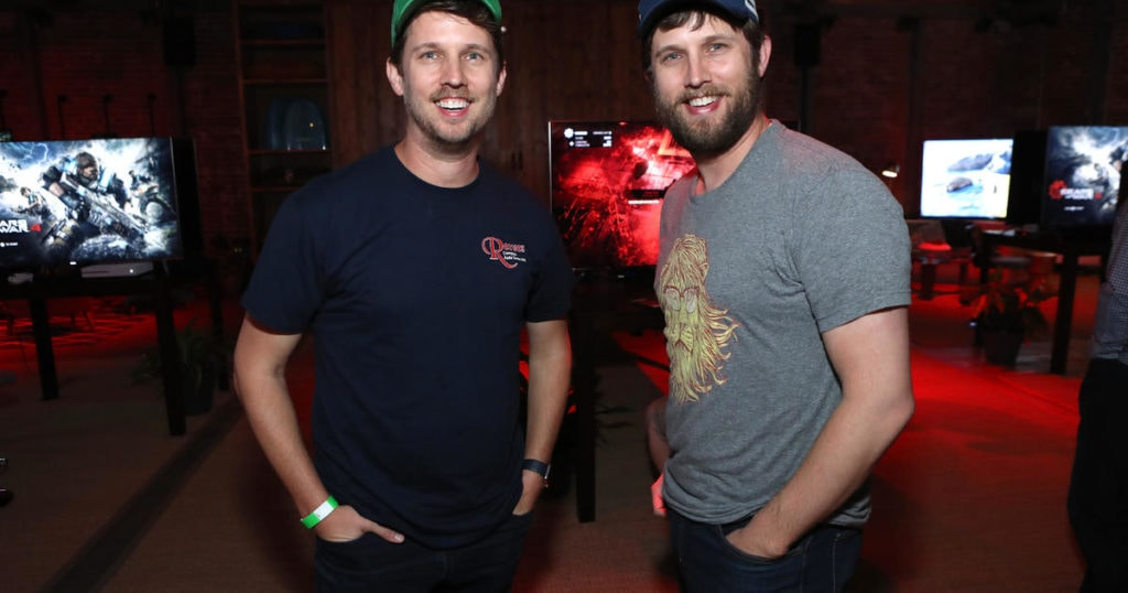 celebrity twins Jon and Dan Heder standing next to one another smiling at the camera