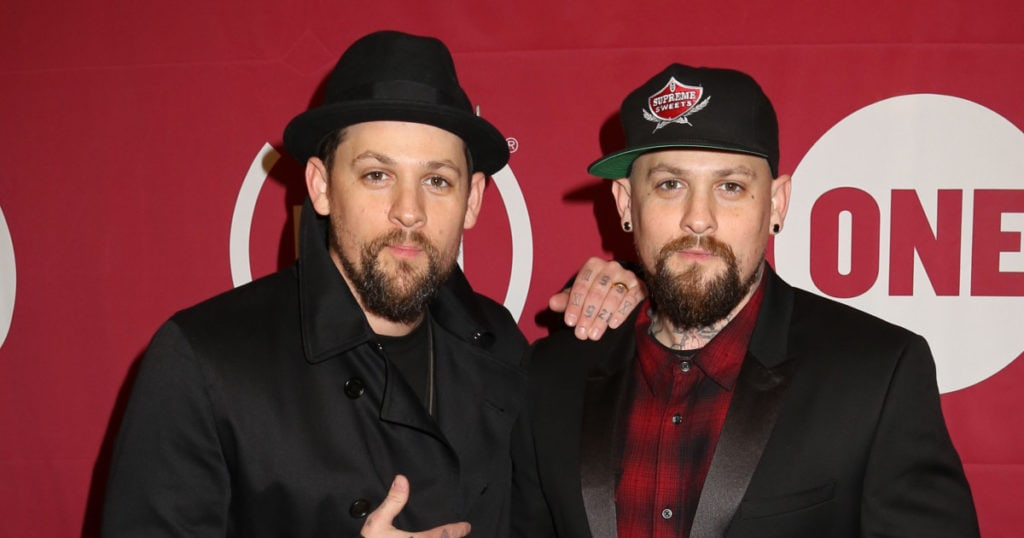 celebrity twins identical twin men posing, 1 with his hand on the others shoulder, each wearing a hat and black clothing.