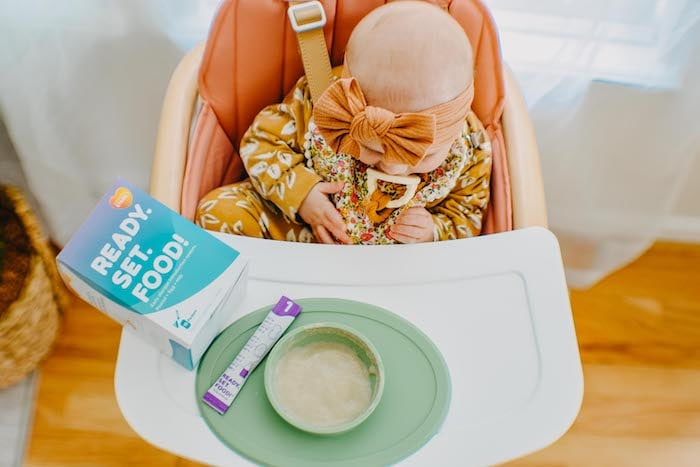baby in a high chair with bowl ready set food allergies for babies