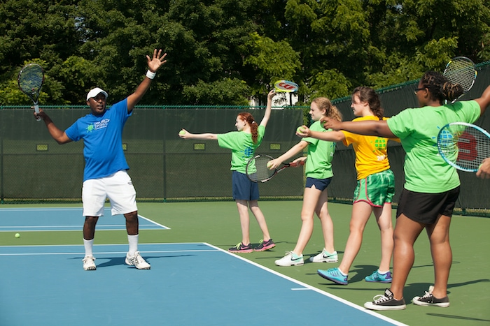 world sports camp girls with a tennis instructor