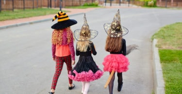 trick or treating COVID three girls wearing halloween costumes walking away down the street