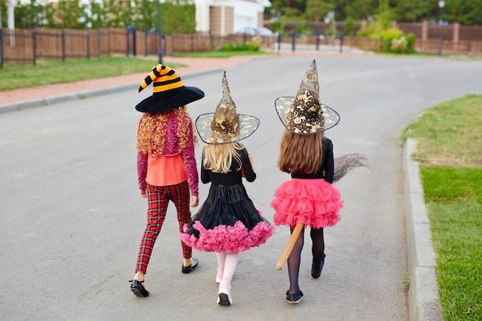 trick or treating COVID three girls wearing halloween costumes walking away down the street