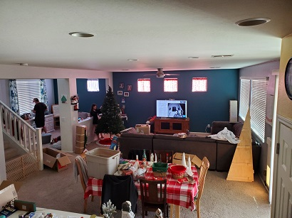 holiday season a wide shot of living room and dining area with people putting out Christmas decorations