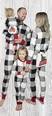 matching Christmas pajamas a man holding a baby and a woman holding hand with a little girl, all 4 in matching pajamas