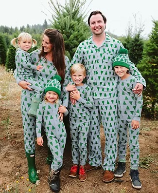 matching christmas pajamas a man and woman smiling with 4 young children, standing in front of a pine tree outside wearing matching pjs