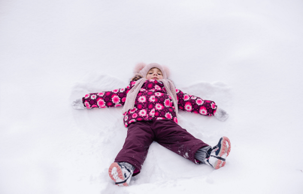 toddler snow boots Girl laying in the snow with a hat, scarf, gloves, boots and coat