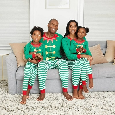 matching christmas pajamas a woman sitting with a girl in her lap and a man with his arm around a boy on a couch wearing matching pjs