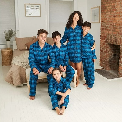 matching christmas pajamas family with matching blue fannel pajamas smiling at a camera