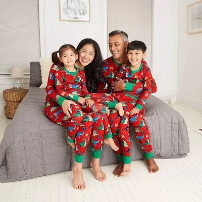 matching christmas pajamas a man with a woman sitting on a bed, each with a small child on their laps, all wearing matchings pjs