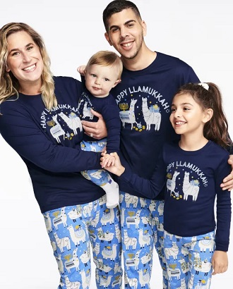 matching christmas pajamas ccouple with a baby and a young girl wearing matching Hanukkah pajamas