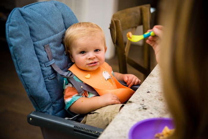 starting baby food baby in a high chair eating food
