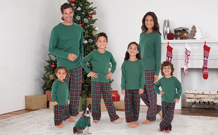 matching christmas pajams a man and woman with 4 children and a dog standing in front of a tree and fireplace with stocking, all dressed in matching pajamas