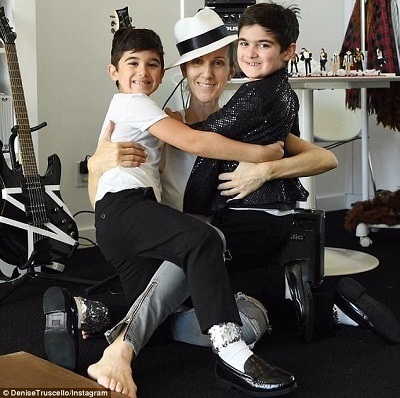 celebrities with twins celine dion with her twins boys, arms around each other and smiling back at the camera in a room with guitars on stands