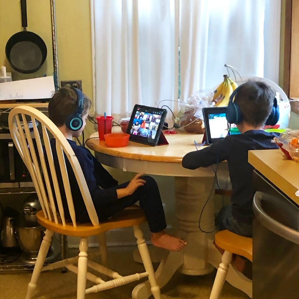two boys sitting at a kitchen table with iPads and headphones on stress during covid