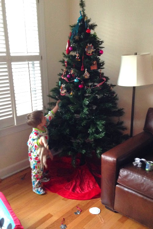 holiday safety tips child standing in front of a Christmas tree with no ornaments on the bottom